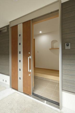 玄関ドアは片引戸で出入りがスムーズ。 正面の飾り棚がアクセントに。
