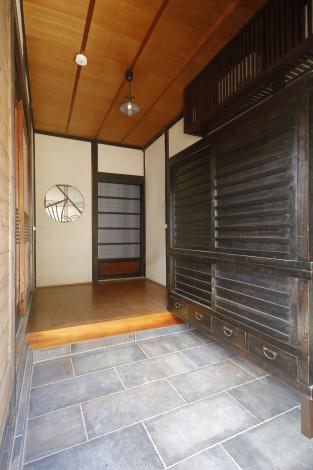 元々の玄関へは実際に古民家で使用されていた「水屋」を下駄箱に活用。 さらにホール正面には古建具を移設し切り嵌めました。 施主様のアイデアとキブネ の技術で色々と活用できました。