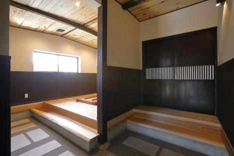 玄関を開くと広い土間。客人の為の囲炉裏スペースと、住居部分に繋がる扉に空間を分けています。